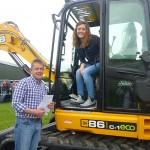 Mervyn McKeown helping Sarah Johnston manage the JCB